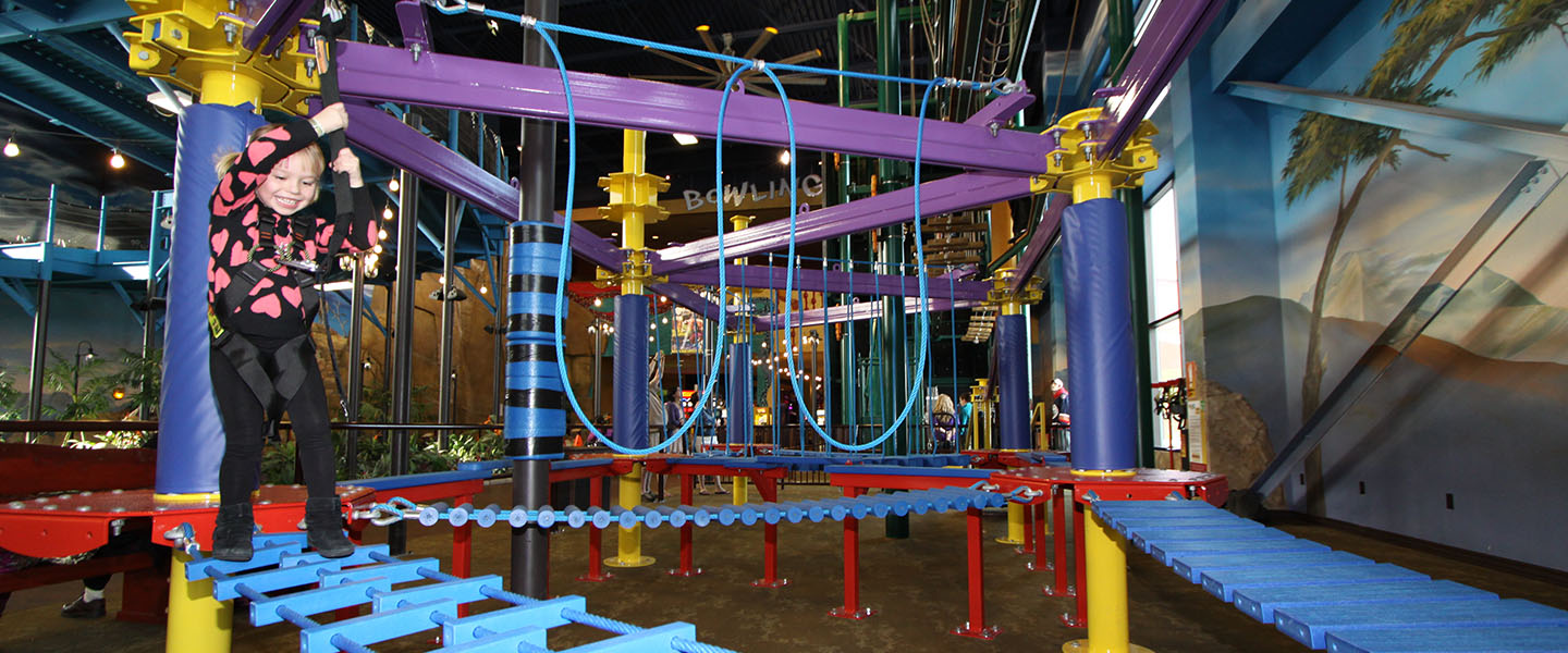little girl climbing on a jungle gym in the indoor theme park