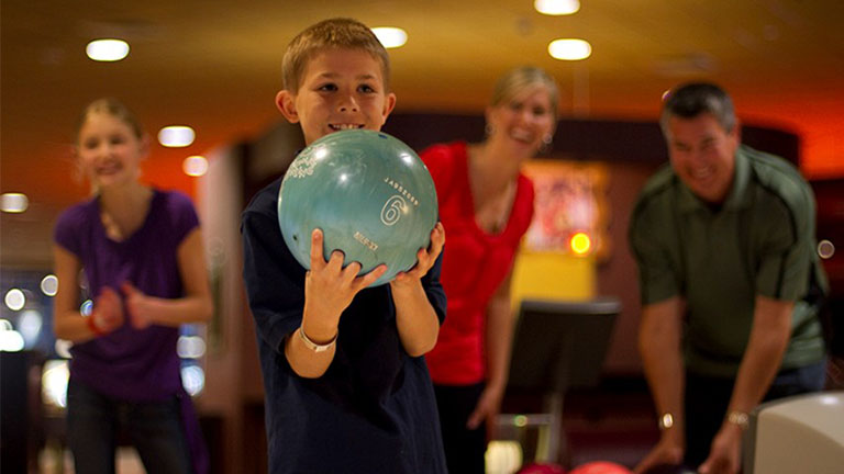 a young boy bowling as his family encourages him