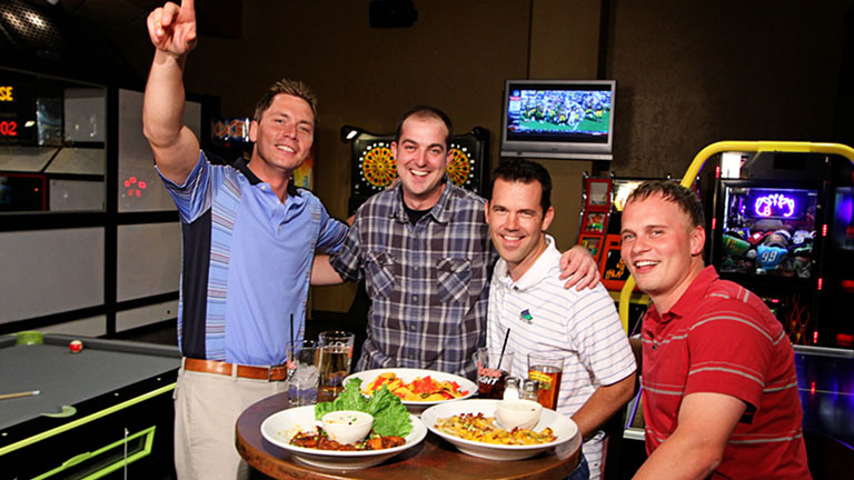 A group of four men enjoying food and drinks while watching sports