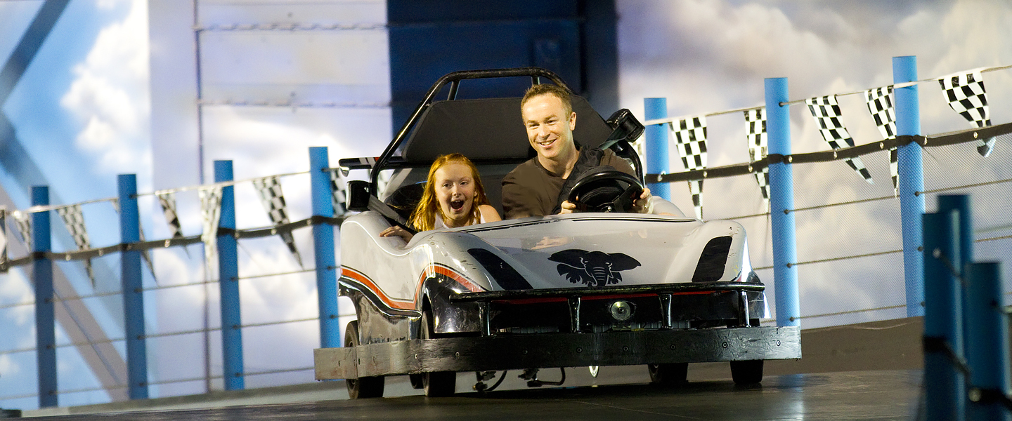 father and daughter riding in the go carts in the indoor theme park