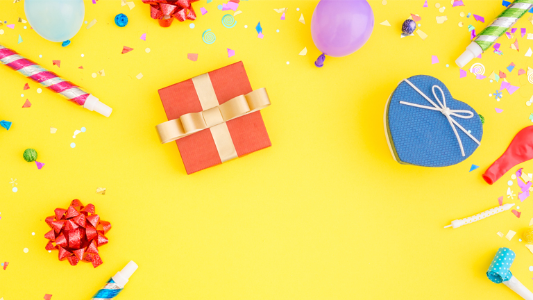 a yellow background with bows, a present, and balloons on it for a birthday theme